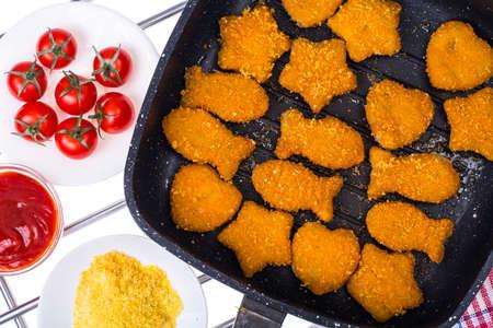 Fried fish sticks in frying pan