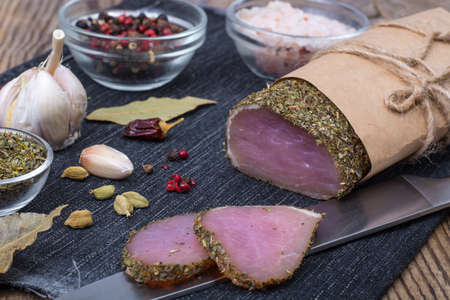 Smoked ham on wooden table with aromatic herbs and spices, natural product