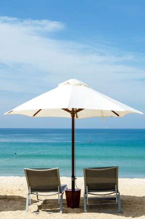 White umbrella and deckchair on the beach