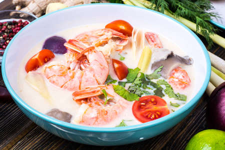 Delicious hot Thai soup Tom Yam with coconut milk and shrimps. Studio Photo Stock Photo