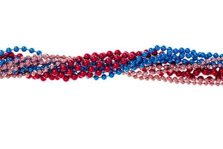 Multi colored shiny mardi gras beads on white background. Studio Photo