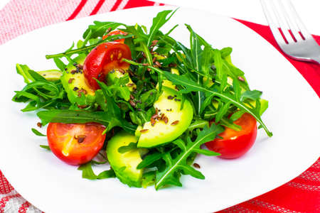 Light dietary salad from arugula, avocado, tomates and flax seed