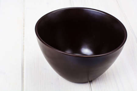 Brown ceramic bowl on white wooden background