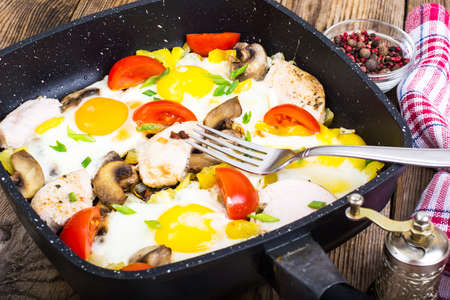 Fried eggs, tomatoes, ham, mushrooms in frying pan. Studio Photo