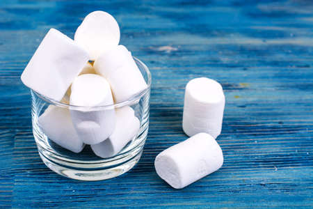 Sweet marshmallow on blue wooden background