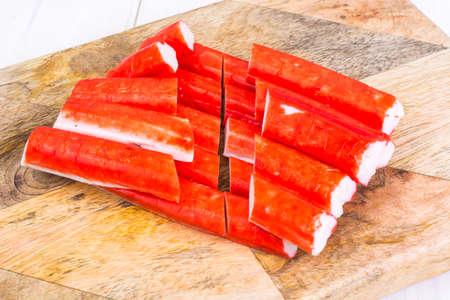 Crab sticks untreated on wooden cutting board