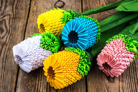 Bouquet of origami flowers on wooden table. Studio Photo Stock Photo