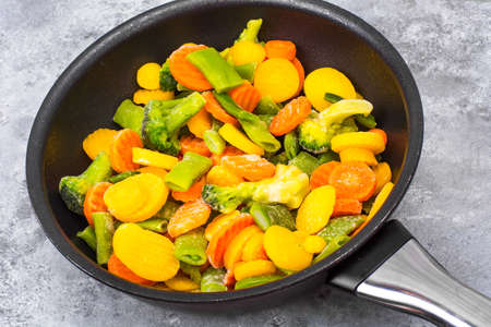 Frozen mix of vegetables in frying pan Stock Photo