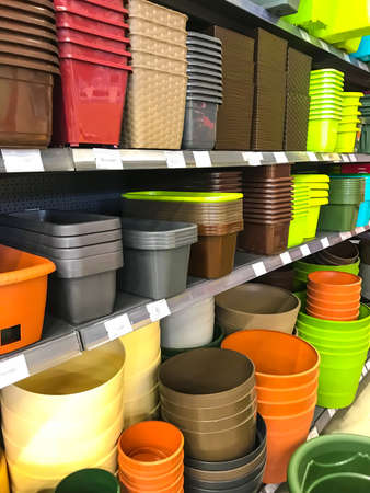Plastic pots and boxes on the shelves in the market Stock Photo