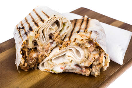 Hot shawarma roll with cheese, meat and sauce. Studio Photo Stockfoto