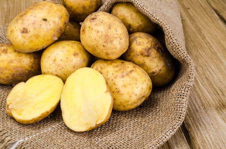 Fresh raw potatoes on wooden surface. Studio Photo