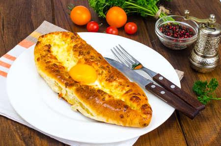 Adjarian khachapuri. Georgian traditional  national cheese  bread with egg.  Homemade food