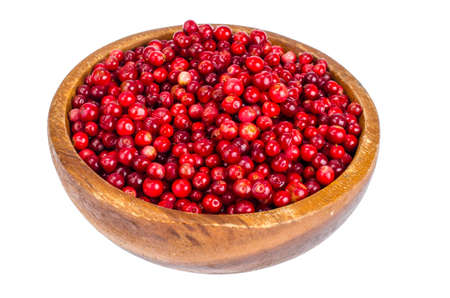 Wooden plate with red bilberry berries on white background. Studio Photo