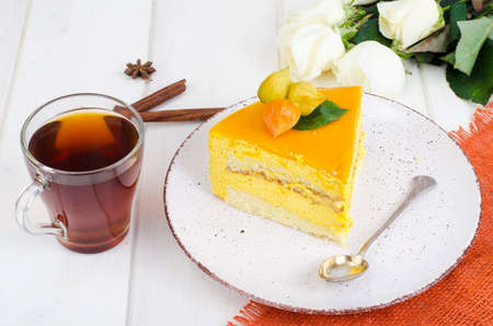Piece of mango mousse cake on plate, white wooden table. Studio Photo 免版税图像 - 114257722