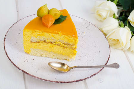 Piece of mango mousse cake on plate, white wooden table. Studio Photo