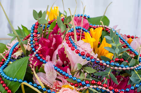 Bouquet of flowers and colored beads for Mardi gras. Studio Photo