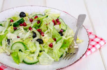 Weight loss. Dietary salad with fresh vegetables and pomegranate seeds. Studio Photo