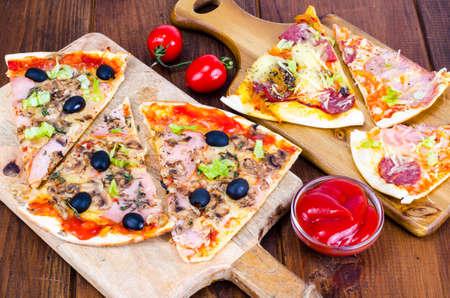 Wooden boards with sliced different pizzas. Studio Photo Foto de archivo - 114259107