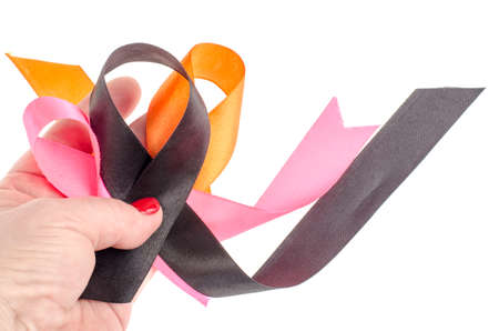 Colorful ribbons on hand, cancer awareness. Studio Photo