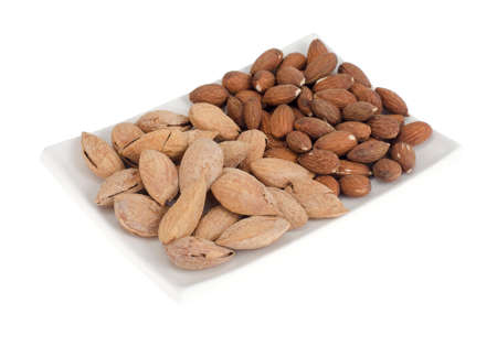 Dried peeled and unpeeled whole almonds on white plate.