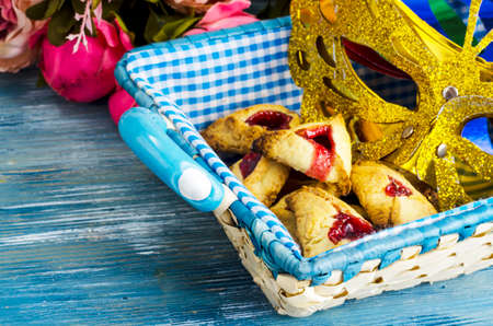 Purim celebration concept (jewish carnival holiday. Homemade cookies Omentasen, carnival mask for celebrating.