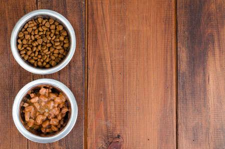 Metal bowls with various pet food. Studio Photo