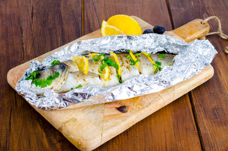 Fish carcass Dicentrarchus labrax with lemon, baked in foil with spices. Studio Photo