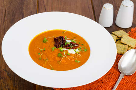 Delicious vegetable cream soup with tomatoes and microgreens. Studio Photo