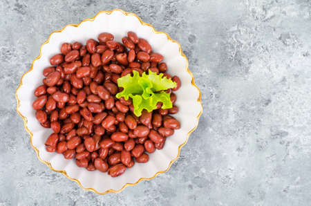Red canned beans in white plate on gray background. Studio Photo Stock Photo