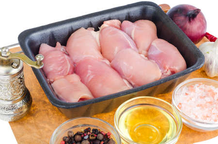 Raw chicken meat in black tray, spices. Studio Photo