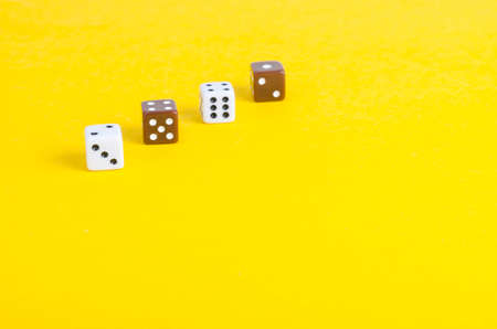 Simple game cubes, dice on bright yellow background. Casino gambling concept 免版税图像