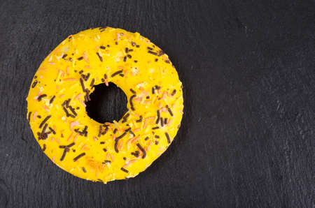 Homemade donuts with colored icing on black background. 免版税图像