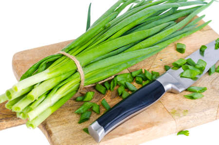 Use of fresh green onions in cooking, kitchen wooden board. Studio Photo