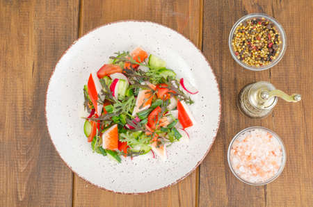 Fresh vegetable salad with crab sticks.