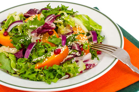 Salad with persimmon and sesame seeds, healthy food.