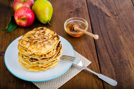 Hot fried pancakes with apples and honey