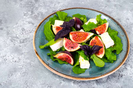 Delicatessen salad with figs and cheese on gray blue background