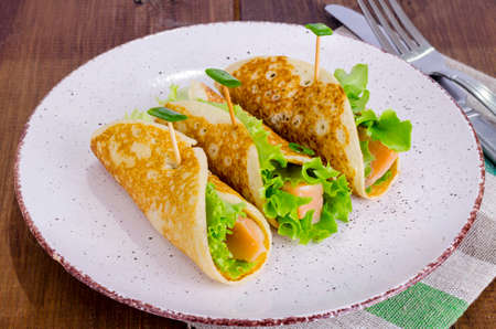 Snack rolls from pancakes, salmon and green salad leaves. Imagens
