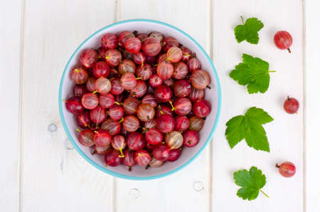 Bowl with red ripe gooseberries on wooden background