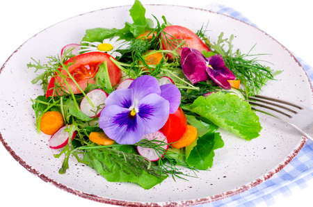 Vegetable salad with edible flowers on white background