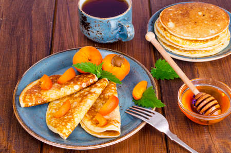 Wheat pancakes with honey and apricots. Photo
