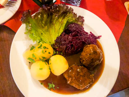 Tasty stewed meat, red cabbage and potato dumplings. Photo Studio