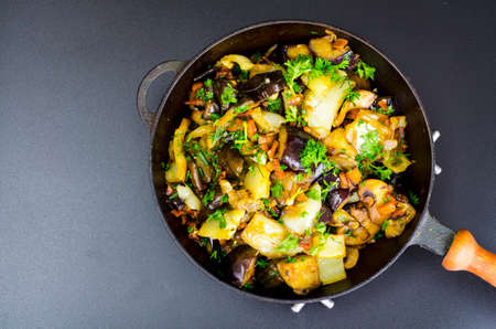 Fried eggplant, paprika and different vegetables in pan on black background. Studio Photo