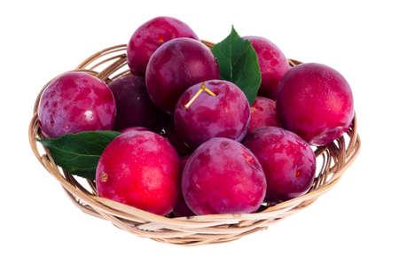 Ripe sweet plums in wicker bowl. Studio Photo