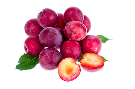 Heap of sweet red plums isolated on white background. Studio Photo