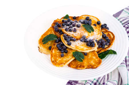Tasty sweet pancakes with sugar and blueberries. Studio Photo