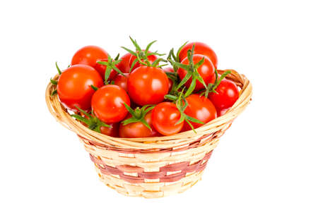Wicker bowl with red tomatoes. Studio Photo