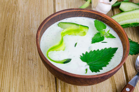 Traditional greek dip sauce or dressing tzatziki prepared with grated cucumber, yogurt, olive oil and fresh dill on wooden table in ceramic bowl. Studio Photo