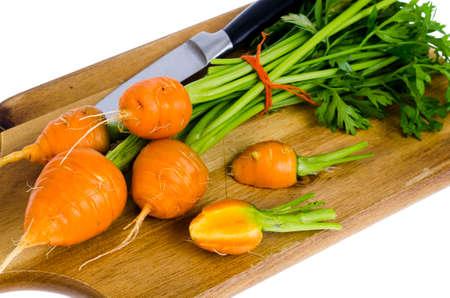 Bouquet de petites carottes rondes (carottes d'héritage parisien) sur fond de bois. Studio photo
