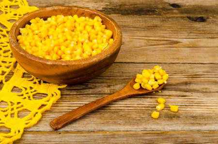 Sweet ripe canned corn in wooden bowl. Studio Photo Imagens